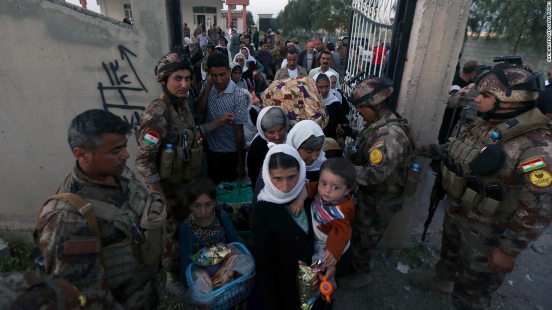 Kurdish Peshmerga army assistance Yazidis as they arrive during a medical core in Altun Kupri, Iraq, on Apr 8.