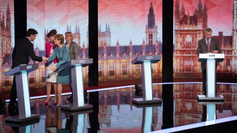 Nigel Farage συγκεντρώνει τις σημειώσεις του, ενώ ο Ed Miliband χειραψία με άλλους ηγέτες των κομμάτων μετά από μια τηλεοπτική συζήτηση εκλογές.