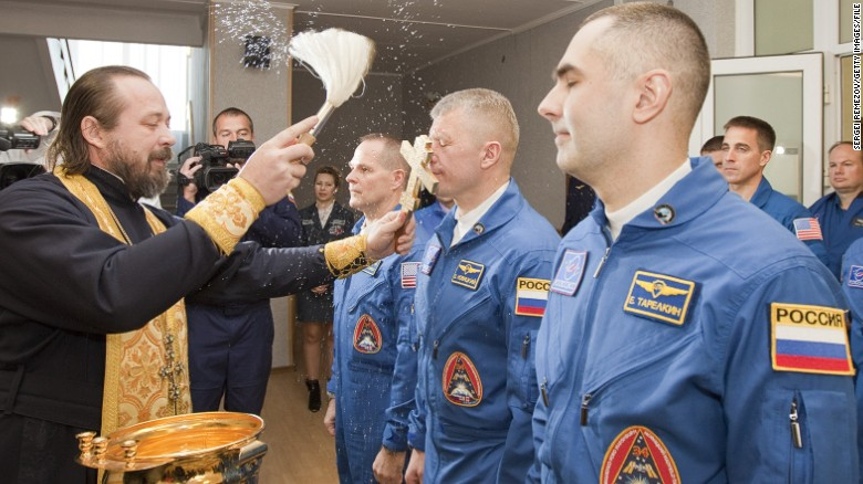 An Orthodox priest blesses the International Space Station crew members -- U.S astronaut Kevin Ford and Russian cosmonauts Oleg Novitskiy and Evgeny Tarelkin -- before launch.