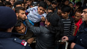 A woman holds a child as hundreds of refugees try to board a train to Vienna at the railway station in Nickelsdorf, Austria, after crossing the Hungarian-Austrian border on September 5. Thousands of refugees stream into Austria from Hungry by the day as Europe continues to grapple with its biggest influx of refugees since WWII.