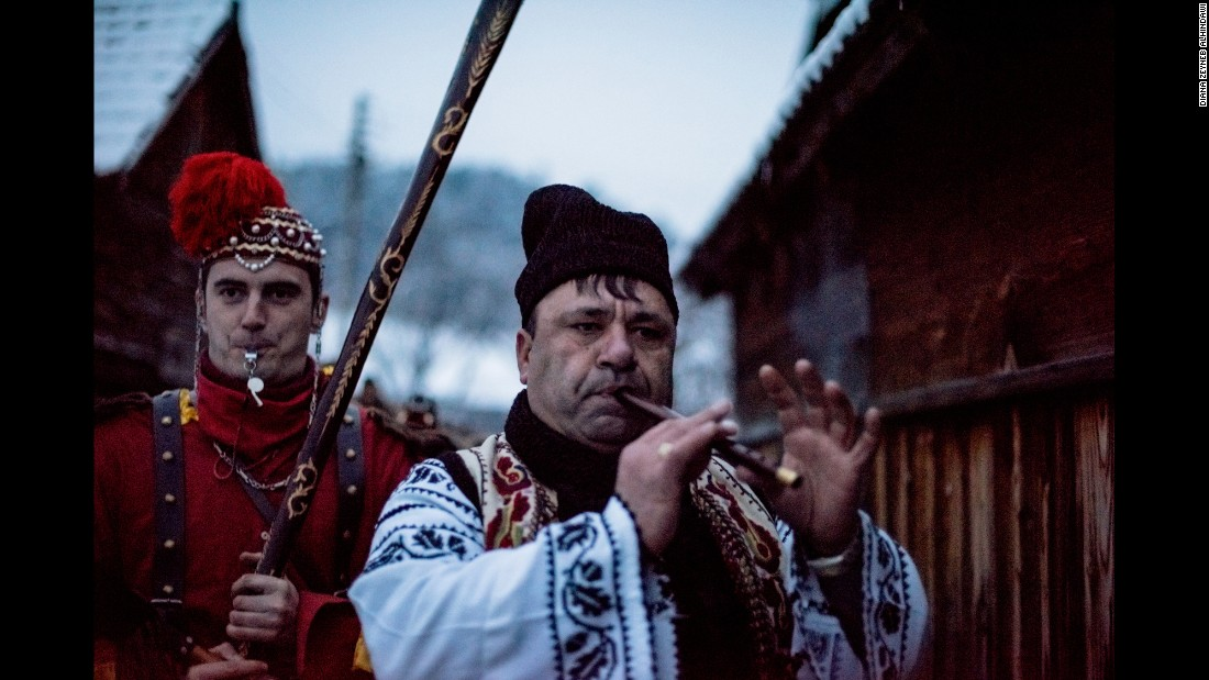 """Dumitru Toloaca, leader of a bear troupe from Laloaia village, marches through the alleys of Asau village.  He's followed closely by his """"bear tamer"""" and """"bears,"""" whom he guides to private homes where they've been invited to perform."""