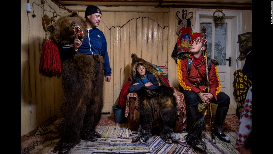 """Catalin Apetroaie chats with a young bear and the """"bear tamer"""" seated on his porch. They and the rest of the troupe have just finished performing for a family and are taking a rest before they continue on to the homes of other patrons."""
