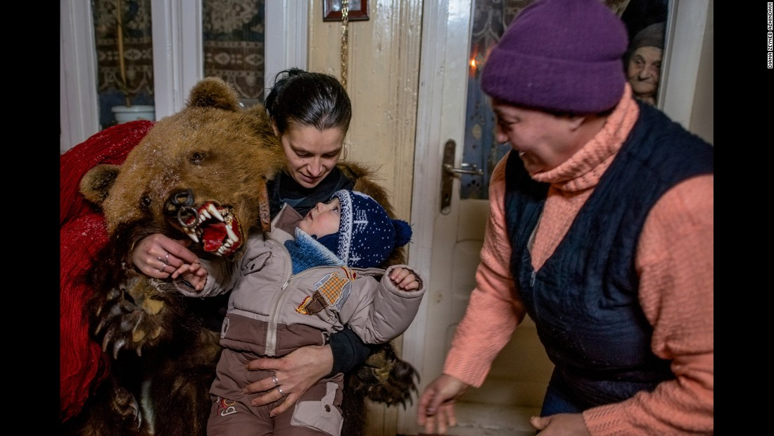 A female bear plays with the young son of Catalin Apetroaie, a bear himself. The child's grandmother scurries by while his great-grandmother peers from inside the house.