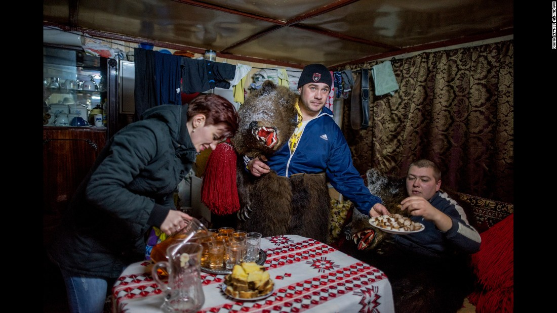 Catalin Apetroaie serves his fellow bears pig fat while his wife fills up glasses of homemade palinka liquor.