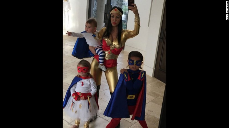 Kourtney Kardashian dressed as Wonder Woman in a red and gold jumpsuit while her three children were done up as mini-superheroes in this family selfie posted to Instagram on Saturday, October 24.