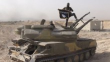 In this image taken from social media, an ISIS fighter holds the group's flag as he stands on a tank, purportedly captured when they took over the town of Qaryatain, Syria. ISIS is one of two groups accounting for 51% of claimed terrorism deaths in 2014.