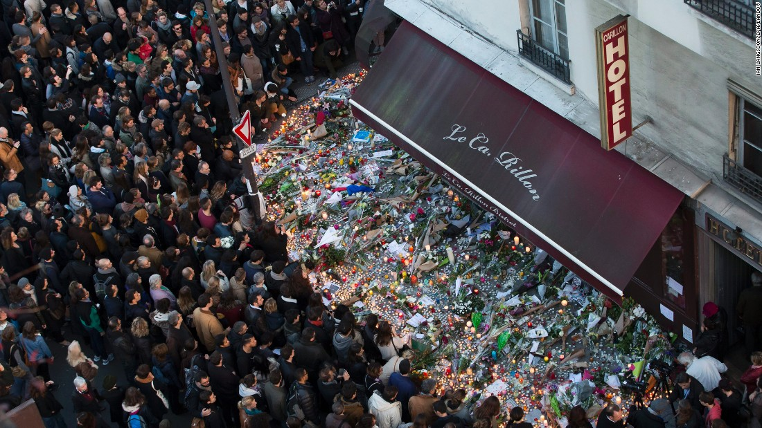 A large crowd gathers to lay flowers and candles in front of the Carillon restaurant, one of the establishments in Paris targeted by terrorists in the November 13 attacks. photos via cnn.com