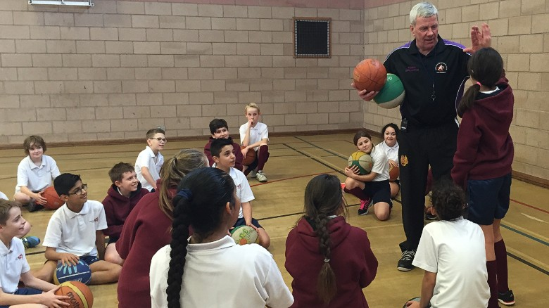 Basketball coach Bob Martin talks to children about the sport.
