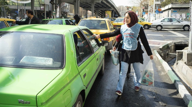 A woman slips campaign material into a car in Tehran.