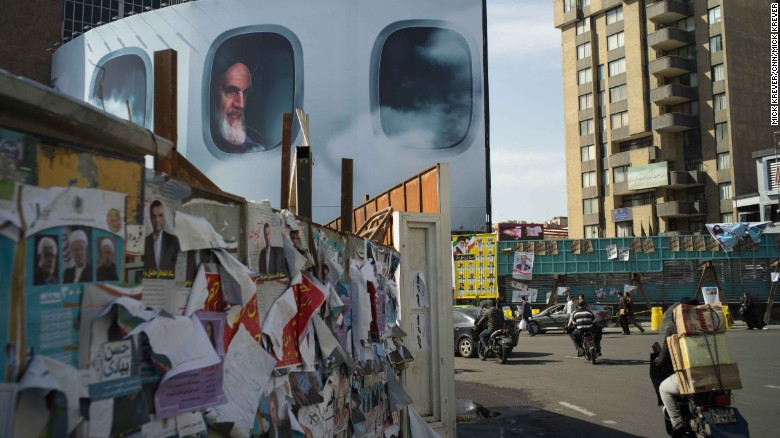 """A picture of Iran's first supreme leader, Ayatollah Ruhollah Khomeini, lurks behind campaign posters in Tehran. Iran is holding elections on Friday, February 26. For the first time, Iranians will vote to elect <a href=""""http://www.cnn.com/2016/01/22/middleeast/iran-elections/"""" target=""""_blank"""">two important government bodies</a> at the same time: the parliament and the Assembly of Experts. The Assembly of Experts chooses the supreme leader."""