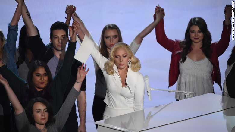 """Lady Gaga, center, after singing """"Til It Happens to You"""" at the Oscars on Sunday."""