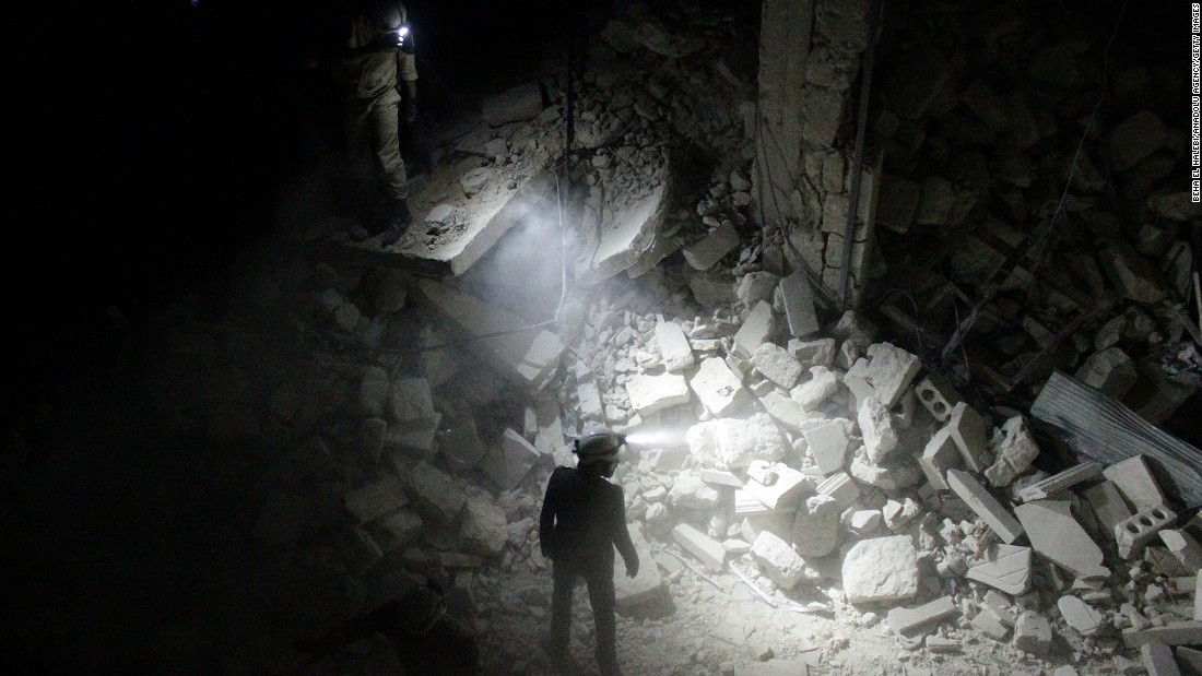 A search team inspects a collapsed building in Aleppo in July.