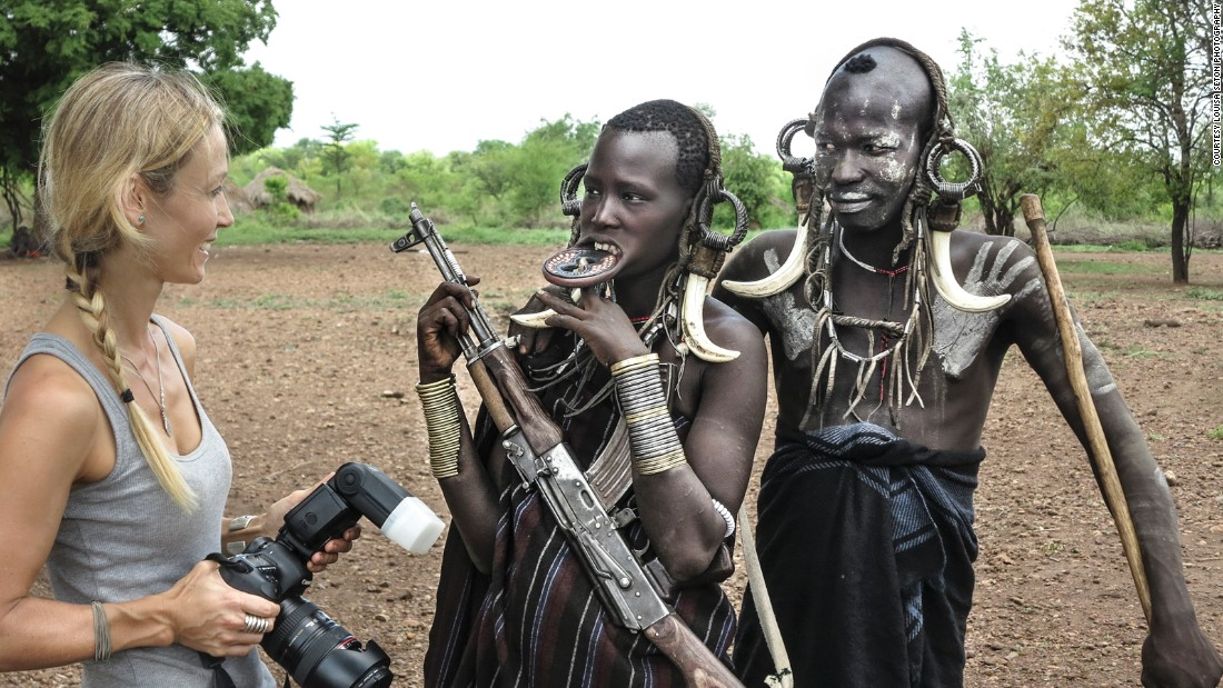 Seton has discussions with the Mursi tribe while taking photographs in their village.