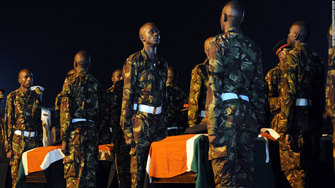 Kenyan soldiers stand over caskets bearing the remains of four slain comrades.