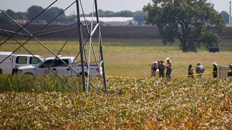 """Investigators surround the scene in a field near Lockhart, Texas where a hot air balloon carrying at least 16 people collided with power lines Saturday, July 30, 2016,  causing what authorities described as a """"significant loss of life.""""  (Ralph Barrera/Austin American-Statesman via AP)"""