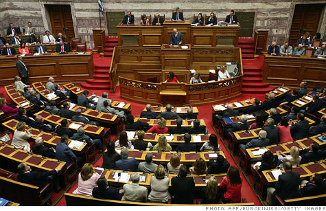 Eurozone finance ministers put the Greece debt crisis on hold by voting for the last phase of a $156 billion bailout.