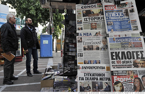 People stand next to an Athens newsstand viewing newspaper bearing headlines on Greece's sovereign debt crisis.