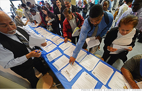 Job seekers pick up open-job fliers from a recruitment specialist in Los Angeles.