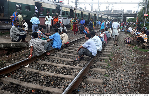 Passengers sit on a railroad track in India waiting for power to return after a massive blackout in late July. Could a serious outage hit the U.S. too if the electrical grid isn't updated?